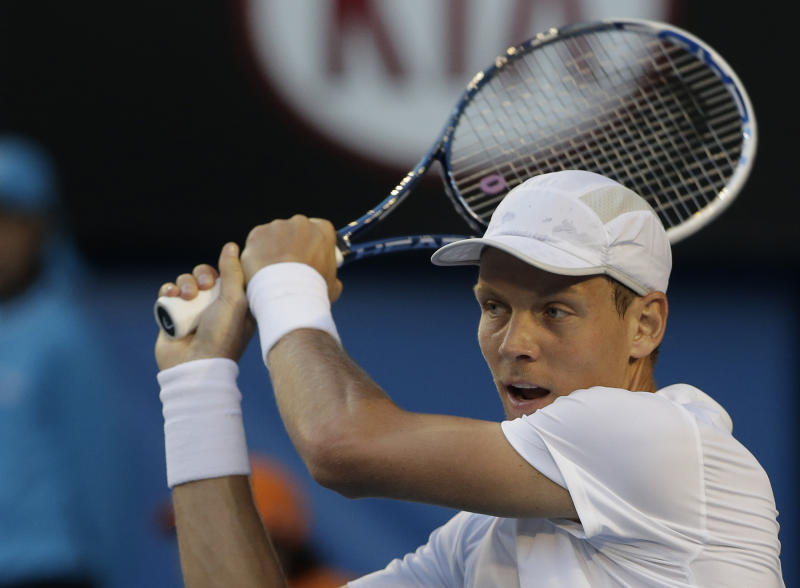 Tomas Berdych of the Czech Republic makes a backhand return to Serbia's Novak Djokovic during their quarterfinal match at the Australian Open tennis championship in Melbourne, Australia, Tuesday, Jan. 22, 2013. (AP Photo/Rob Griffith)
