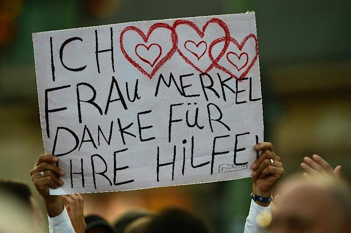 """A Syrian refugee holds up a placard which reads """"I love you Mrs Merkel. Thank you for your help"""" in Berlin on September 14, 2016 (AFP Photo/Tobias Schwarz)"""