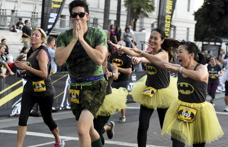 Runners chase after the Riddler during the Batman Inaugural 5K run on Batman's 80th anniversary at Grand Park on Saturday, Sept. 21, 2019, in Los Angeles. (Keith Birmingham/The Orange County Register via AP)