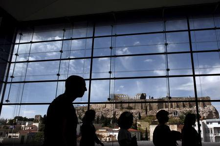 FILE PHOTO: Tourists  are silhouetted as they walk inside the Acropolis Museum with the temple of Parthenon on the background in Athens, April 25, 2015. REUTERS/Kostas Tsironis/File Photo