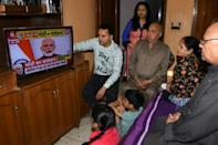 A family watches Indian Prime Minister Narendra Modi's address to the nation on television at their home in Amritsar (AFP Photo/NARINDER NANU)