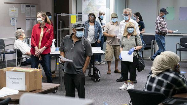 PHOTO: Voters wearing protective masks stand in line to cast ballots at an early voting polling location for the 2020 Presidential elections in Fairfax, Va., Sept. 18, 2020. (Bloomberg via Getty Images)