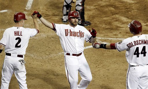 Arizona Diamondbacks' Jason Kubel gets high-fives from teammates Aaron Hill (2) and Paul Goldschmidt (44) after scoring a run against the Houston Astros during the fifth inning in a baseball game Friday, July 20, 2012, in Phoenix. (AP Photo/Ross D. Franklin)