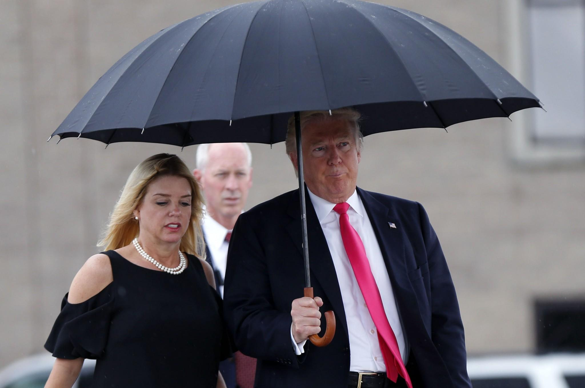 Republican presidential candidate Donald Trump walks in the rain with Florida Attorney General Pam Bondi, as they arrive at a campaign rally in Tampa, Fla., on Aug. 24, 2016. (Photo: Gerald Herbert/AP)