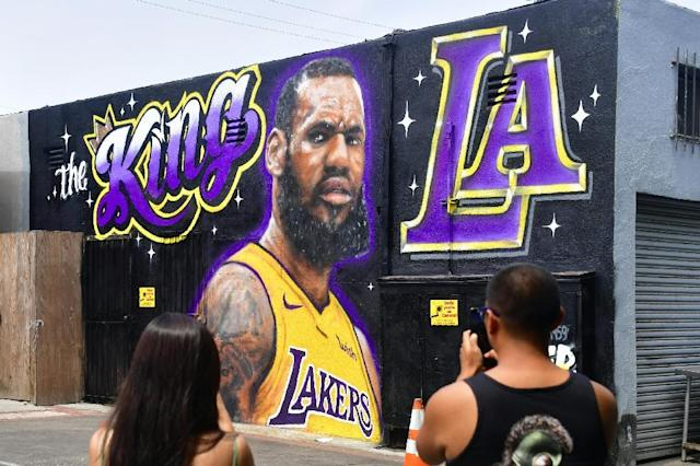 People photograph a mural of LeBron James in a Los Angeles Lakers jersey painted by Jonas Never and Menso One in Venice, California to welcome James to his new team (AFP Photo/Frederic J. BROWN)