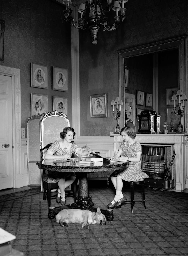 Queen Elizabeth II and Princess Margaret studying whilst a corgi sleeps at their feet in a drawing room at Windsor Castle, Berkshire, 1940.