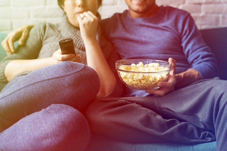 Man and woman watching TV together on sofa with popcorn.