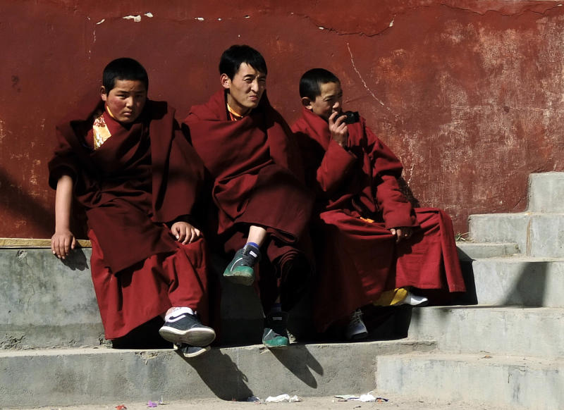 In this photo taken Tuesday, Feb. 7, 2012, young Tibetan monks watch monks perform a religious ceremony at a monastery in Jiuzhaigou, in northwestern China's Sichuan province. Tibet's exiled government in India called on Tibetans this year to shun celebrations for their traditional new year, which started Wednesday, Feb. 22, 2012. Instead, Tibetans are urged to pray for those living under Chinese rule. (AP Photo/Andy Wong)