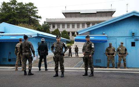 U.S. and South Korean soldiers, foreground, and North Korean soldiers, background, stand guard next to the meeting rooms that straddle the border between the two Koreas - Credit:  SeongJoon Cho/Bloomberg