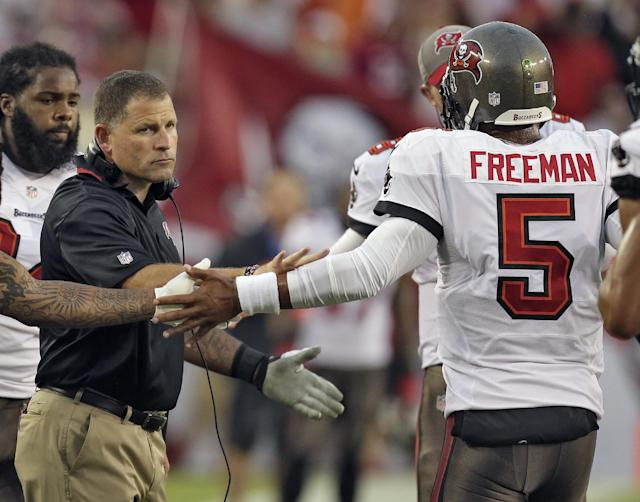 FILE - In this Sept. 15, 2013 file photo, Tampa Bay Buccaneers head coach Greg Schiano, left, shakes hands with quarterback Josh Freeman (5) after Freeman threw a touchdown pass to wide receiver Kevin Ogletree during the first quarter of an NFL football game against the New Orleans Saints, in Tampa, Fla. The Buccaneers have benched Freeman and replaced him with rookie Mike Glennon. The move Wednesday, Sept. 25, 2013, came two days after Schiano insisted Freeman remained the starter because he gave the team the best chance to win. (AP Photo/Chris O'Meara, File)