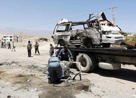 Afghan policemen work at the site of a suicide attack in west of Kabul, Afghanistan May 25, 2016. REUTERS/Mohammad Ismail