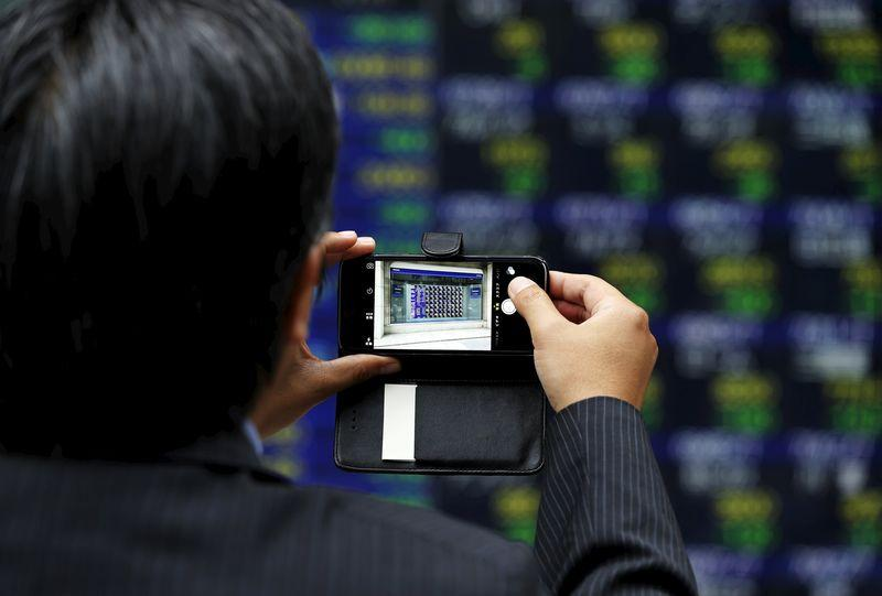 A man takes a photo of an electronic stock quotation board with his smartphone outside a brokerage in Tokyo