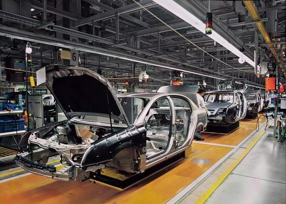 Car frames on an assembly line.