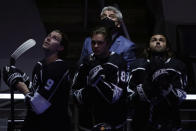 Los Angeles Kings head coach Todd McLellan, top, looks up during the national anthem along with some of his players before an NHL hockey game against the St. Louis Blues, Friday, March 5, 2021, in Los Angeles. (AP Photo/Marcio Jose Sanchez)