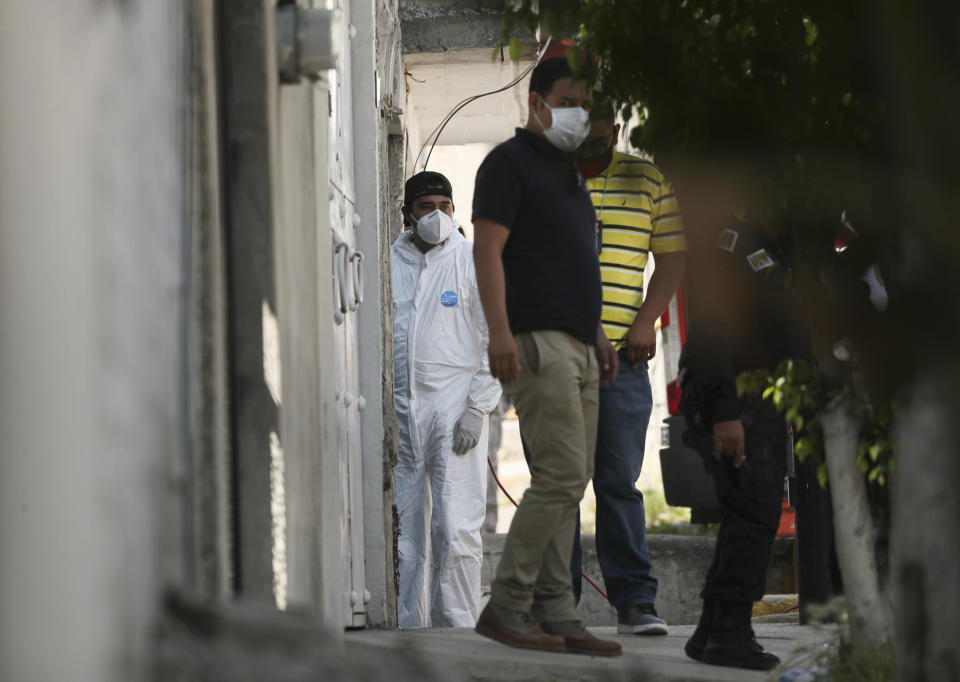 A forensic investigator stands at the entrance of a house where police found bones under the floor in the Atizapan municipality of the State of Mexico, Thursday, May 20, 2021. Police have turned up bones and other evidence under the floor of the house where a man was arrested for allegedly stabbing a woman to death and hacking up her body. (AP Photo/Fernando Llano)