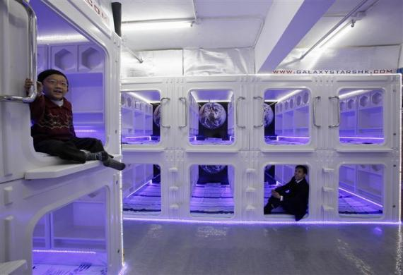 Eric Wong (R), managing director of a capsule bed manufacturer, and his son Osbert pose in modified capsule beds inside a showroom in Hong Kong January 7, 2012.