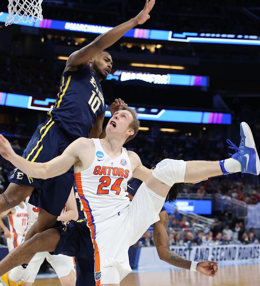 <p>ETSU player Isaac Banks (10) towers over Florida guard Canyon Barry (24) during their first round game in the NCAA men's basketball tournament on Thursday, March 16, 2017 at the Amway Center in Orlando, Fla. (Stephen M. Dowell/Orlando Sentinel/TNS via Getty Images) </p>