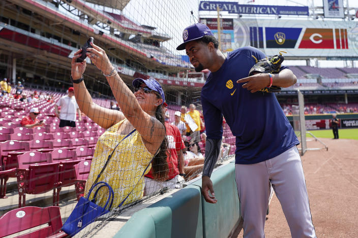 Milwaukee Brewers' relief pitcher Jandel Gustave (31) poses for a photograph with Milwaukee Brewers' fan Michelle Dortch before a baseball game against the Cincinnati Reds in Cincinnati, Sunday, July 18, 2021. (AP Photo/Bryan Woolston)