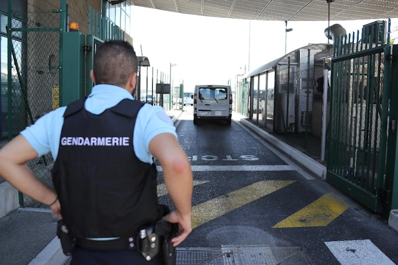 A French gendarme watches as a van carrying a group of Russian football fans arrives at the international airport in Nice on June 18, 2016, before the fans are flown back to Moscow