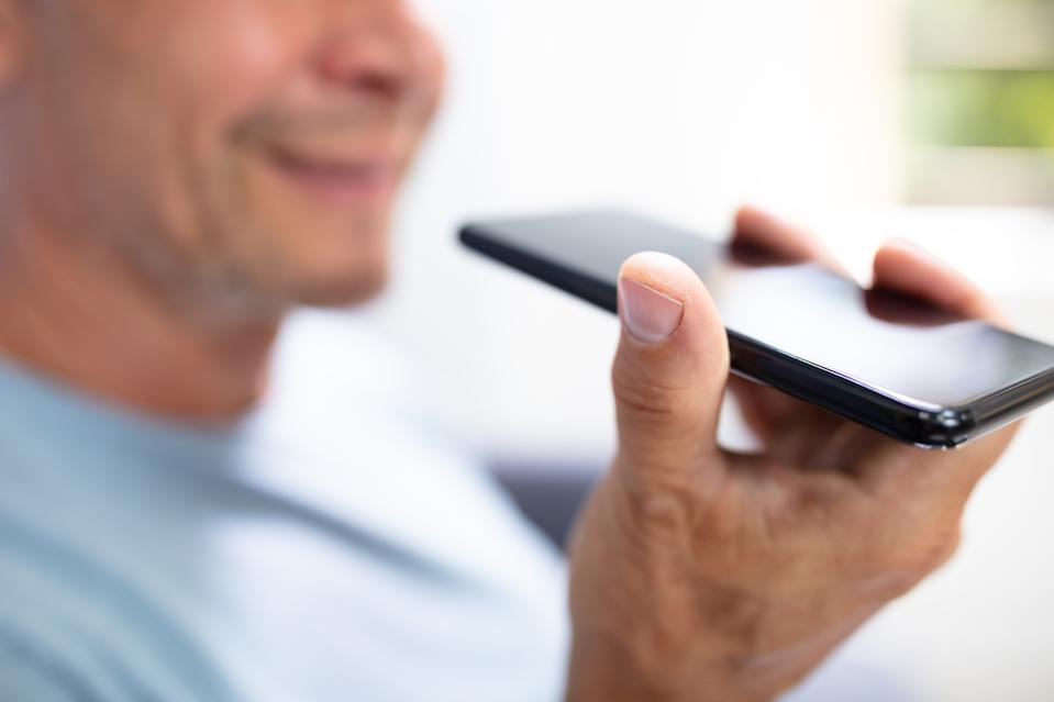Close-up Of A Beard Man Using Voice Recognition Function On Mobile Phone Against White Background