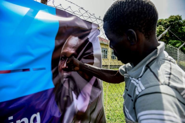 A man punches a banner bearing a picture of Dominic Ongwen