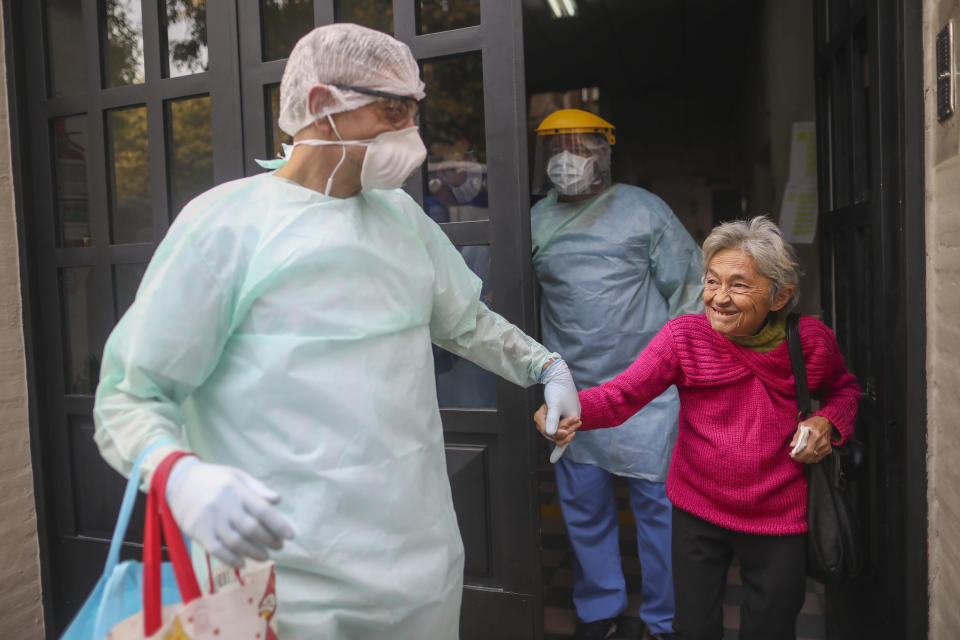 FILE - In this April 22, 2020 file photo, medical staff evacuate an elderly woman from a nursing home after multiple residents of the facility tested positive for the COVID-19 coronavirus in Buenos Aires, Argentina. Argentina reached 1 million confirmed coronavirus cases on Monday, Oct. 19, 2020, according to the Ministry of Health. (AP Photo/Natacha Pisarenko, File)