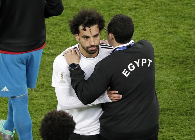 A Egypt's team official comforts Egypt's Mohamed Salah after the group A match between Russia and Egypt at the 2018 soccer World Cup in the St. Petersburg stadium in St. Petersburg, Russia, Tuesday, June 19, 2018. (AP Photo/Dmitri Lovetsky)