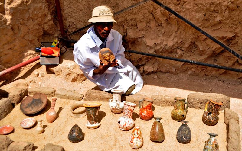 An archaeologists shows artifacts discovered in a 3,500-year-old tomb in the Draa Abul Nagaa necropolis, near the southern Egyptian city of Luxor, on April 18, 2017 - AFP