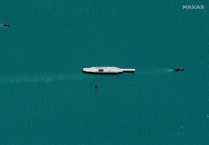 Iran's refurbished mockup aircraft carrier is seen towed by a tugboat near Bandar Abbas
