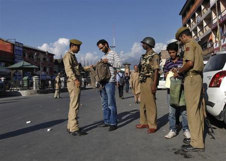 Police search the belongings of Kashmiri men during a cordon and search operation ahead of a concert by the Bavarian State Orchestra and renowned conductor Zubin Mehta in Srinagar September 5, 2013. REUTERS/Danish Ismail
