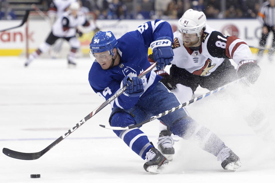 Toronto Maple Leafs defenseman Tyson Barrie (94) turns hard with the puck as Arizona Coyotes right wing Phil Kessel (81) defends during the first period of an NHL hockey game, Tuesday, Feb. 11, 2020 in Toronto. (Nathan Denette/The Canadian Press via AP)
