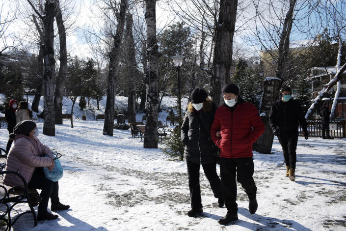 People walk in the snow-covered Kugulu Park public garden, in Ankara, Turkey, Monday, Jan. 18, 2021. Winter storms and snowfalls remains in effect for a large swath of Turkey, causing road accidents and closure of roads between cities and villages in many regions, hours after the snow falls blanketed the country. (AP Photo/Burhan Ozbilici)