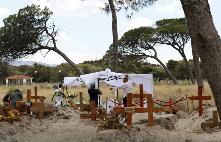 Workers prepare for a COVID-19 burial in the Maitland cemetery in Cape Town, South Africa, Tuesday, Jan. 19, 2021. The City of Cape Town is working closely with the Muslim Judicial Council to increase burial capacity as COVID-19 claims more lives in a second surge of the pandemic. (AP Photo/Nardus Engelbrecht)