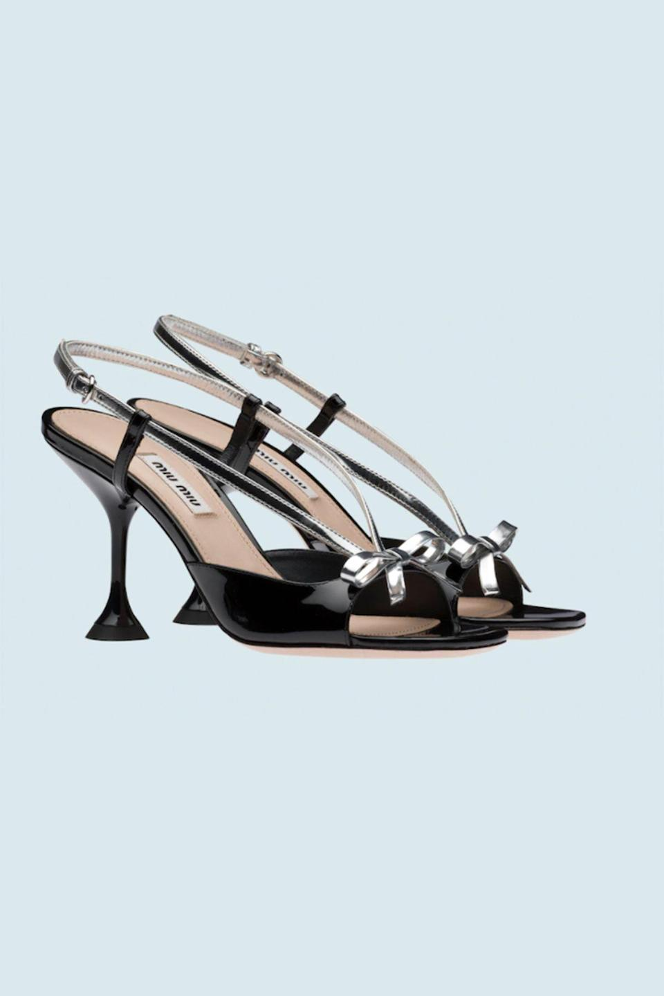 """<p><strong>Miu Miu</strong></p><p>miumiu.com</p><p><strong>$890.00</strong></p><p><a href=""""https://www.miumiu.com/us/en/shoes/sandals/products.patent_leather_and_metallic_technical_fabric_sandals.5X398D_3LE9_F0I89_F_M085.html"""" rel=""""nofollow noopener"""" target=""""_blank"""" data-ylk=""""slk:Shop Now"""" class=""""link rapid-noclick-resp"""">Shop Now</a></p><p>A pyramid heel and patent silver bows jazz up these slingbacks with Great Gatsby-esque flair. </p>"""