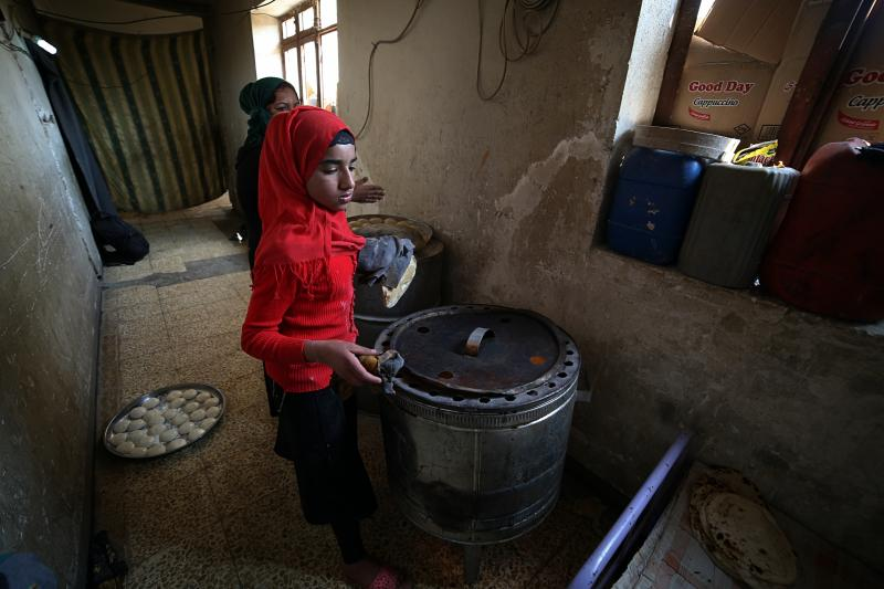 In this March 18, 2019 photo, Um Yusuf, a widow of an Islamic State group militant, and her daughter make bread to sell, in Mosul, Iraq. Thousands of Iraqi families face crushing social and legal discrimination -- all because of the choices their male relatives made under the Islamic State group's rule. Um Yusuf cannot get social assistance, and her teenage son Omar is being turned away from jobs. (AP Photo/Farid Abdulwahed)