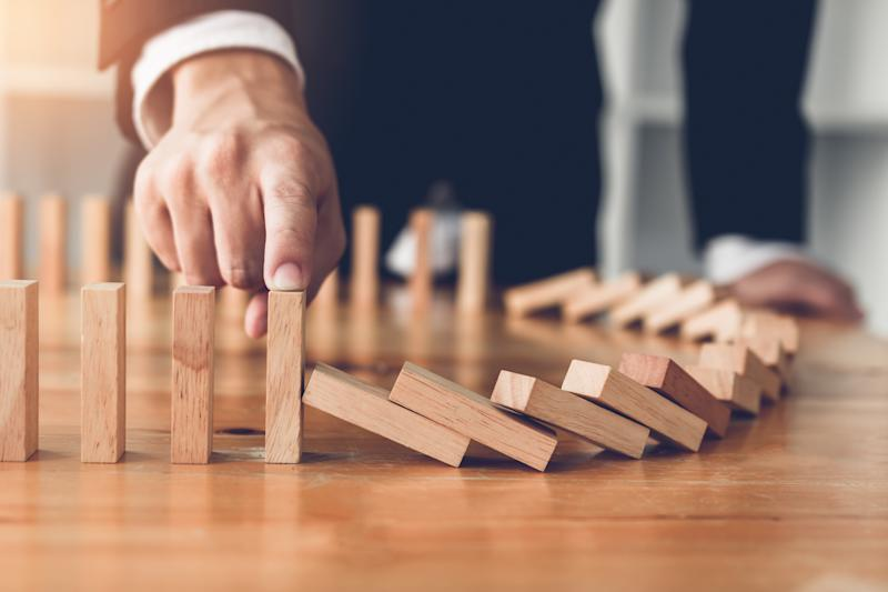 A businessman knocks down wooden dominoes.