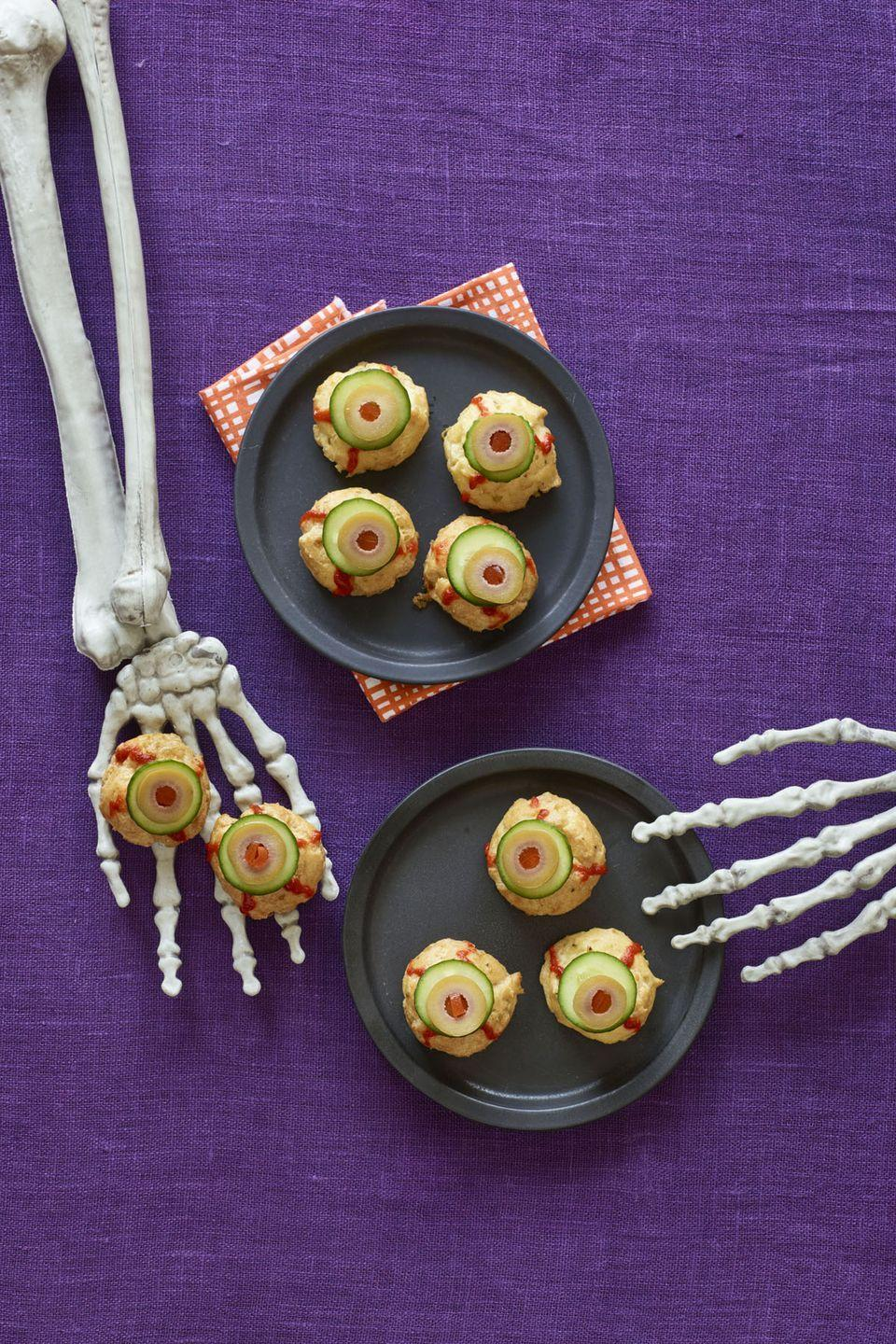 """<p>Top these cheese pastry puffs with slices of cucumber, olives, and squiggles of spicy Sriracha for a Halloween treat you won't be able to take your eyes off.</p><p><em><strong><a href=""""https://www.womansday.com/food-recipes/recipes/a60165/bitesize-eyeballs-recipe/"""" rel=""""nofollow noopener"""" target=""""_blank"""" data-ylk=""""slk:Get the Bite-Size Eyeballs recipe."""" class=""""link rapid-noclick-resp"""">Get the Bite-Size Eyeballs recipe.</a></strong></em></p>"""