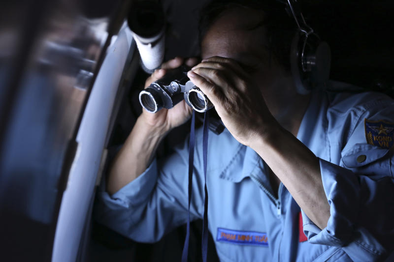 Vietnamese Air Force Col. Pham Minh Tuan uses binoculars on board a flying aircraft during a mission to search for the missing Malaysia Airlines flight MH370 in the Gulf of Thailand over the location where Chinese satellite images showed possible debris from the missing Malaysian jetliner, Thursday, March 13, 2014. (AP Photo)