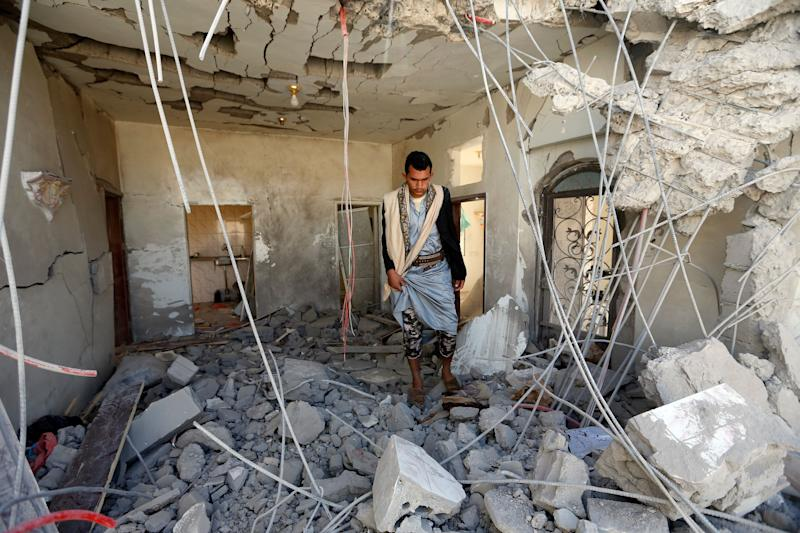 A Yemeni man inspects the damage in the aftermath of a reported air strike by the Saudi-led coalition in the Yemeni capital Sanaa on March 8, 2018.