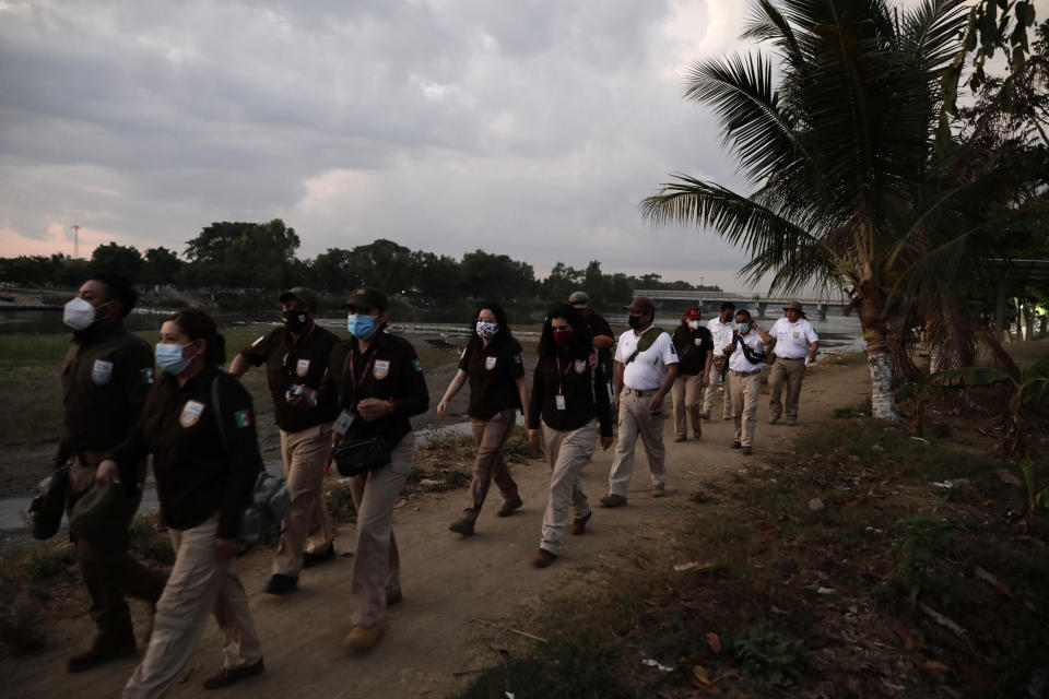 Mexican immigration agents walk towards an access point to the Suchiate River, the natural border between Guatemala and Mexico, near Ciudad Hidalgo, Mexico, Sunday, March 21, 2021. Mexico sent hundreds of immigration agents, police and National Guard to its southern border to launch an operation to crack down on migrant smuggling. (AP Photo/Eduardo Verdugo)