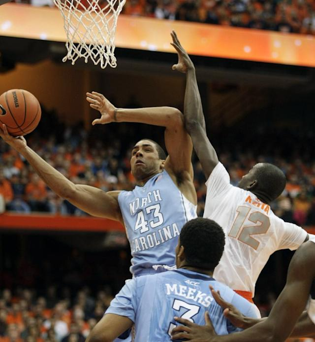North Carolina's James Michael McAdoo, left, shoots against Syracuse's Baye Moussa Keita, right, in the first half of an NCAA college basketball game in Syracuse, N.Y., Saturday, Jan. 11, 2014. (AP Photo/Nick Lisi)