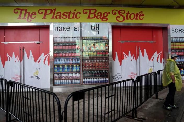 A man stands outside the Plastic Bag Store, a pop-up to raise awareness of the environmental issues with plastics