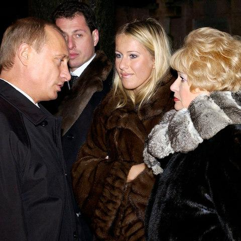 Vladimir Putin speaks with Ms Sobchak and her mother in 2003 at the grave of her father, former St Petersburg mayor Anatoly Sobchak. - Credit: Government Pool Photo via AP