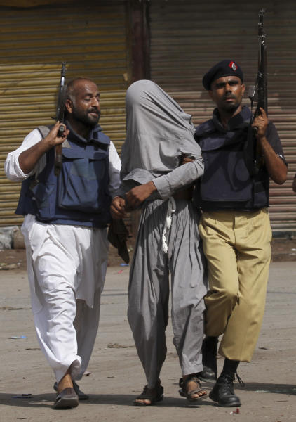 FILE - In this Friday, April 27, 2012, file photo, Officers of Pakistani law enforcing agency escort an alleged criminal during a crackdown operation against criminals in Karachi's town of Lyari, Pakistan. Over 2,000 people were murdered in Pakistan's largest city last year, but the shooting death of 20-year-old Shahzeb Khan in one of Karachi's most upscale neighborhoods sparked an unusual outcry and highlighted a growing trend of citizens using social media to hold the country's rich and powerful to account. (AP Photo/Shakil Adil, File)