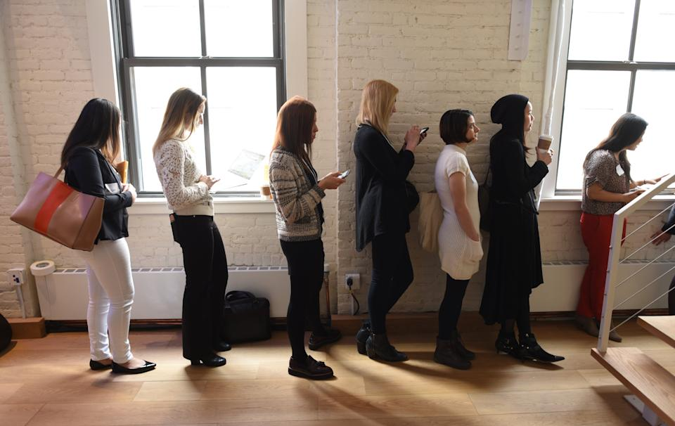 """Women line up to have Facebook profile pictures taken during a Facebook event called """"Finding A Job Or Hiring On Facebook"""" in New York February 28, 2018. The event helps people find  jobs and help local businesses hire the right people, by expanding the ability to apply to jobs directly on Facebook to more than 40 countries. / AFP PHOTO / TIMOTHY A. CLARY        (Photo credit should read TIMOTHY A. CLARY/AFP via Getty Images)"""