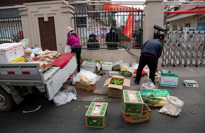 Grocery vendors sell vegetables outside a residential compound which has been blocked off by authorities amid an outbreak of COVID-19 in Shijiazhuang, Hebei province, China, January 19, 2021. / Credit: STRINGER/Reuters