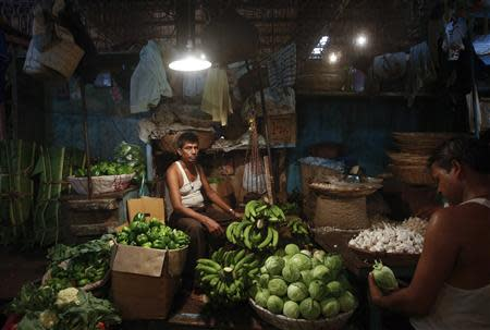 A vendor waits for customers at his stall at a wholesale food market in Mumbai