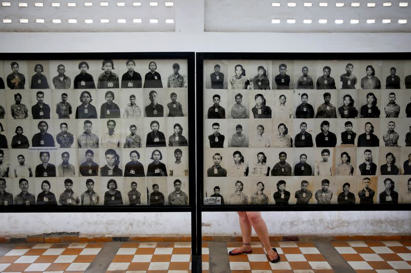 A visitor looks at pictures of victims of Khmer Rouge regime at the former notorious Tuol Sleng prison that is now the Genocide Museum, in Phnom Penh