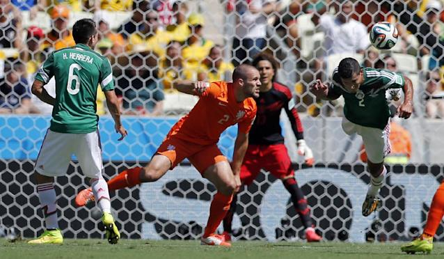 Mexico's Francisco Rodriguez, right, heads the ball clear during the World Cup round of 16 soccer match between the Netherlands and Mexico at the Arena Castelao in Fortaleza, Brazil, Sunday, June 29, 2014. (AP Photo/Wong Maye-E)