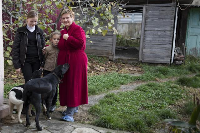 In this photo taken on Wednesday, Nov. 27, 2013, Alexandra Krivchenko, right, and her children, center, play with the dogs in the yard of a house sandwiched between the railway and a federal highway (seen in the background) in the village of Vesyoloye outside Sochi, Russia. As the Winter Games are getting closer, many Sochi residents are complaining that their living conditions only got worse and that authorities are deaf to their grievances. (AP Photo/Alexander Zemlianichenko)